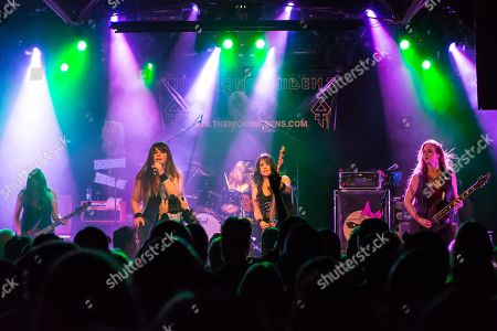 Stock Picture of The American women's metal band The Iron Maidens, tribute band of the British heavy metal band Iron Maiden live in the Schueuer Lucerne, Switzerland vocals Kirsten Rosenberg drumset Linda McDonald guitar Courtney Cox guitar Nita Strauss