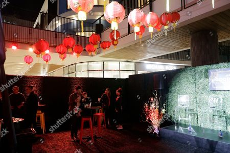Harry Shum Jr. Decorations are placed over patrons during the opening of a Lunar New Year installation in Santa Monica, Calif. In recent years, the Lunar or Chinese New Year, which people around the globe are ringing in Tuesday, seems to have achieved all-American status. Major companies are celebrating, and capitalizing, on a holiday that at its heart is about being with loved ones and wishing for prosperity and good luck
