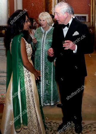 Britain's Prince Charles and Camilla Duchess of Cornwall meet former cricketer Isa Guha, left, at the British Asian Trust Dinner at Buckingham Palace.