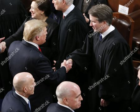 Stock Photo of US President Donald J. Trump (L) shakes hands with Supreme Court Justice Brett M. Kavanaugh (R) as he arrives to deliver his second State of the Union address from the floor of the House of Representatives on Capitol Hill in Washington, DC, USA, 05 February 2019.