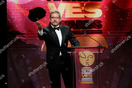 "Stock Photo of Actor Steve Carell wears a mask of his character ""Felonious Gru"" from the Minions movies as he presents the VES lifetime achievement award to CEO of Illumination Entertainment Chris Meledandri during the 17th annual VES Awards at the Beverly Hilton Hotel"
