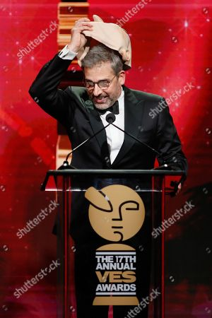 "Stock Image of Actor Steve Carell wears a mask of his character ""Felonious Gru"" from the Minions movies as he presents the VES lifetime achievement award to CEO of Illumination Entertainment Chris Meledandri during the 17th annual VES Awards at the Beverly Hilton Hotel"