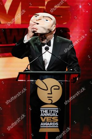"Actor Steve Carell wears a mask of his character ""Felonious Gru"" from the Minions movies as he presents the VES lifetime achievement award to CEO of Illumination Entertainment Chris Meledandri during the 17th annual VES Awards at the Beverly Hilton Hotel"