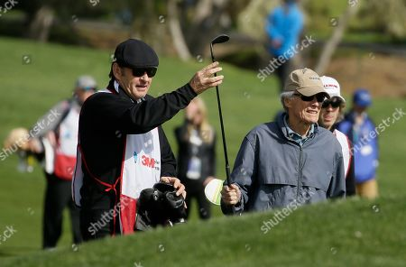 Nick Faldo, Clint Eastwood. Nick Faldo, working as a caddie, left, hands Clint Eastwood a club near the third green during the celebrity challenge event of the AT&T Pebble Beach National Pro-Am golf tournament, in Pebble Beach, Calif