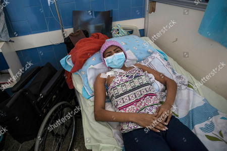 "Carmen Perez, 21, who has a tumor in one of her lungs, lies in a bed in the Vargas Public Hospital in Caracas, Venezuela. Almost 1,000 kilometers (620 miles) away, in the Colombian border city of Cucuta, opponents of Maduro are hastily putting together plans with U.S. officials to open a ""humanitarian corridor"" to deliver emergency food and medical supplies"