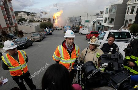 San Francisco fire chief Joanne Hayes-White, second from right, listens as Pacific Gas and Electric spokesperson Paul Doherty, center, speaks to reporters about a fire on Geary Boulevard in San Francisco