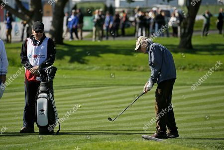 Clint Eastwood chips the ball to the third green as caddie Nick Faldo, left, looks on during the celebrity challenge event of the AT&T Pebble Beach National Pro-Am golf tournament, in Pebble Beach, Calif