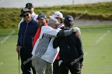 Ray Romano, right, is embraced by Daniel Lawrence Whitney, known professionally as Larry the Cable Guy on the 17th green during the celebrity challenge event of the AT&T Pebble Beach National Pro-Am golf tournament, in Pebble Beach, Calif. Looking on from left are Andy Garcia and Colt Ford
