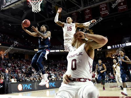 Connecticut's Tarin Smith (2) drives to the basket against Temple's Nate Pierre-Louis (15) and Alani Moore II (0) during the second half of an NCAA college basketball game, in Philadelphia. Temple won 81-63