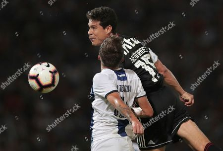 Hernanes of Brazil's Sao Paulo, top, fights for the ball with Nahuel Tenaglia of Argentina's Talleres during a Copa Libertadores soccer match in Cordoba, Argentina