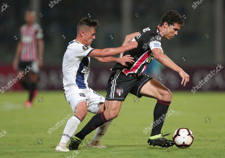 Hernanes of Brazil's Sao Paulo, right, fights for the ball with Andres Cubas of Argentina's Talleres during a Copa Libertadores soccer match in Cordoba, Argentina