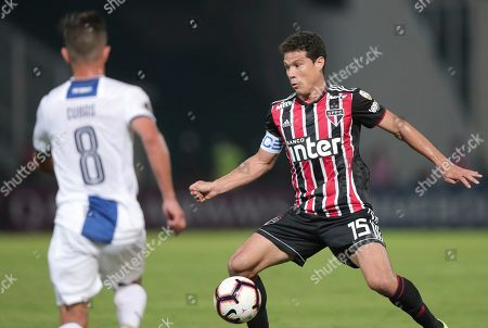 Hernanes of Brazil's Sao Paulo fights for the ball with Andres Cubas of Argentina's Talleres during a Copa Libertadores soccer match in Cordoba, Argentina