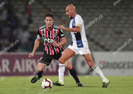Pablo Ginazu of Argentina's Talleres, right, fights for the ball with Hernanes of Brazil's Sao Paulo during a Copa Libertadores soccer match in Cordoba, Argentina