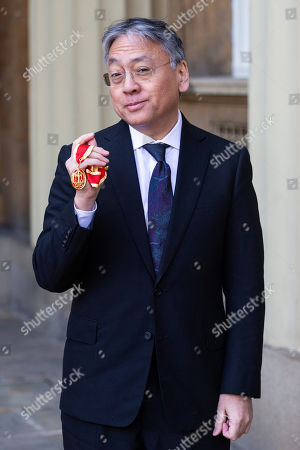 Author Sir Kazuo Ishiguro poses with his Knights Bachelor Medal after being knighted at an investiture by HRH The Prince of Wales at Buckingham Palace in London.