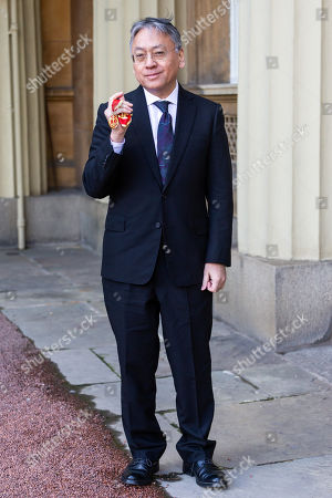 Stock Photo of Author Sir Kazuo Ishiguro poses with his Knights Bachelor Medal after being knighted at an investiture by HRH The Prince of Wales at Buckingham Palace in London.