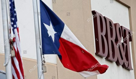 The American Flag and Texas State Flag hang outside an exterior of a BB&T bank branch in Rockwall, Texas, USA, 07 February 2019. Media reports on 07 February 2019 state SunTrust and BB&T banks are to merge in a 66 billion US dollar deal, creating a bank with 442 billion US dollar in assets. Both banks said the merger would enable them to save net costs of some 1.6 billion USD by 2022. BB&T chairman and chief executive Kelly King is to keep his title and position in the merged entity until 2021 when SunTrust chief William Rogers takes over as group chied executive.