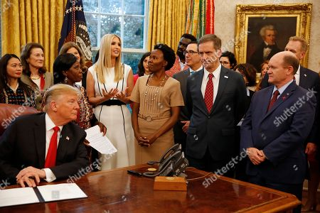 "First Daughter and Advisor to the President Ivanka Trump makes remarks prior to United States President Donald Trump signing the National Security Presidential Memorandum to Launch the ""Women's Global Development and Prosperity"" Initiative in the Oval Office of the White House in Washington, DC. Listening at far right is United States Senator Christopher A. Coons (Democrat of Delaware)."
