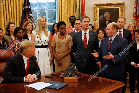 "United States Senator Christopher A. Coons (Democrat of Delaware) makes remarks prior to US President Donald Trump signing the National Security Presidential Memorandum to Launch the ""Women's Global Development and Prosperity"" Initiative in the Oval Office of the White House in Washington, DC. Standing at left center listening to Senator Coons is First Daughter and Advisor to the President Ivanka Trump."