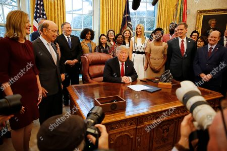 "United States President Donald Trump makes remarks prior to signing the National Security Presidential Memorandum to Launch the ""Women's Global Development and Prosperity"" Initiative in the Oval Office of the White House in Washington, DC. Among those attending the ceremony are: US Secretary of Commerce Wilbur Ross Jr., US Secretary of State Mike Pompeo, First Daughter and Advisor to the President Ivanka Trump, and US Senator Christopher A. Coons (Democrat of Delaware)."