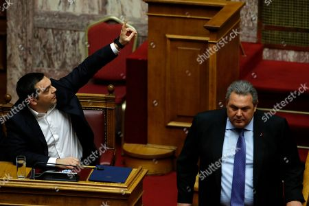 Alexis Tsipras, Panos Kammenos. Greece's Prime Minister Alexis Tsipras, left, raises his hand as former defense minister Panos Kammenos leaves the podium during a parliament session in Athens, . Greek lawmakers are set Friday to approve Macedonia's NATO accession, ending a process to normalize relations between the two neighbors and anchor the country ? renamed North Macedonia ? firmly within the western sphere of influence