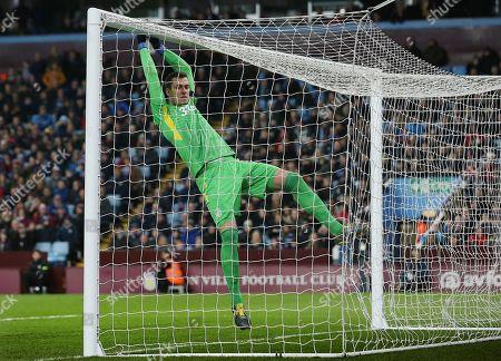 Aston Villa goalkeeper Lovre Kalinic swings on the cross bar