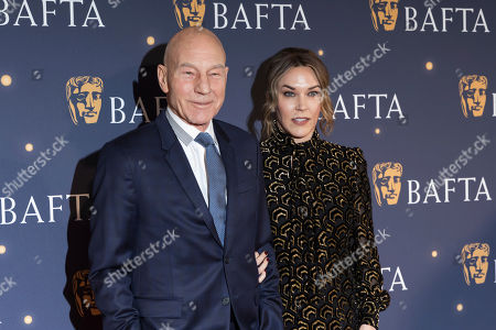 Patrick Stewart, Sunny Ozell. Actor SIr Patrick Stewart, left and partner musician Sunny Ozell pose for photographers on arrival at a BAFTA Fundraising Gala, in London