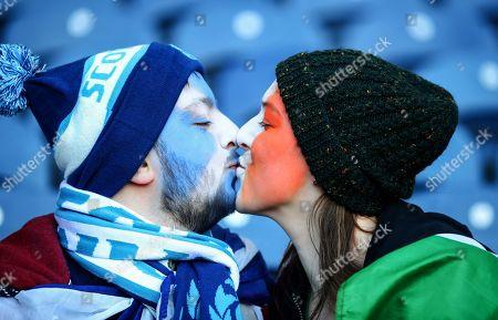 Stock Picture of Scotland vs Ireland. Scotland fan Frazer Grant with Ireland fan Sarah Greene