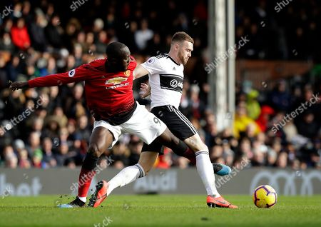 Manchester United's Romelu Lukaku, left, duels for the ball with Fulham's Calum Chambers during the English Premier League soccer match between Fulham and Manchester United at Craven Cottage stadium in London