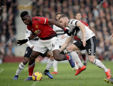 Stock Photo of Manchester United's Paul Pogba, left, duels for the ball with Fulham's Calum Chambers during the English Premier League soccer match between Fulham and Manchester United at Craven Cottage stadium in London