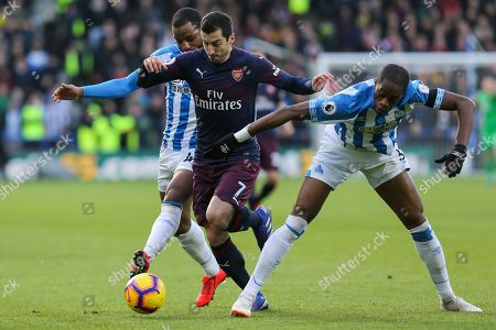Arsenal midfielder Henrikh Mkhitaryan (7) runs with the ball and is challenged by Huddersfield Town defender Terence Kongolo (5) and Huddersfield Town midfielder Jason Puncheon (42) during the Premier League match between Huddersfield Town and Arsenal at the John Smiths Stadium, Huddersfield