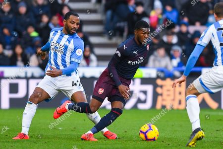 Ainsley Maitland-Niles of Arsenal (15) gets past Jason Puncheon of Huddersfield Town (42) during the Premier League match between Huddersfield Town and Arsenal at the John Smiths Stadium, Huddersfield