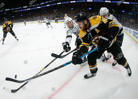 Boston Bruins' David Krejci battles for the puck with Los Angeles Kings' Dion Phaneuf during the third period of an NHL hockey game, in Boston