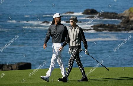 Stock Photo of Larry Fitzgerald Jr., Adrian Young. Larry Fitzgerald Jr., left, and Adrian Young walk down the ninth fairway of the Pebble Beach Golf Links during the third round of the AT&T Pebble Beach Pro-Am golf tournament, in Pebble Beach, Calif