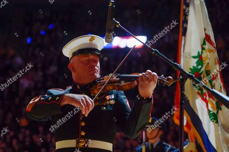 """Master Gunnery Sergeant Peter Wilson of """"The President's Own"""" United States Marine Band performs the national anthem on his violin before an NCAA college basketball game in Morgantown, W.Va. on"""