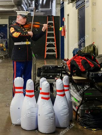 """Master Gunnery Sgt. Peter Wilson of """"The President's Own"""" United States Marine Band practices his violin before performing the national anthem at an NCAA college basketball game between West Virginia and Texas in Morgantown, W.Va"""