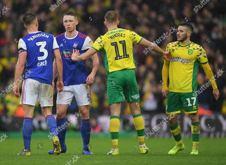 Jordan Rhodes of Norwich City separates Matthew Pennington, Jonas Knudsen of Ipswich Town from Emi Buendia of Norwich City
