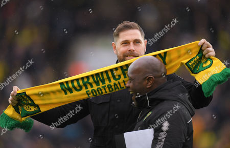 Stock Image of Former Norwich City player Grant Holt uses his scarf to polish the head of the stadium announcer