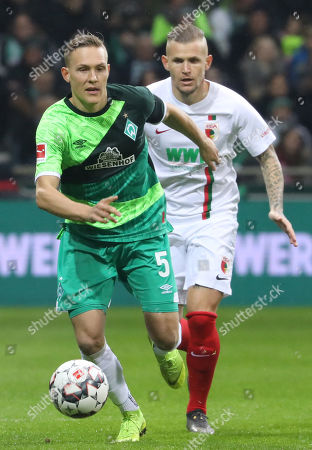 Bremen's Ludwig Augustinsson (L) in action against Augsburg's Alfred Finnbogason (R)  during the German Bundesliga soccer match between Werder Bremen and FC Augsburg  in Bremen, Germany, 10 February 2019.