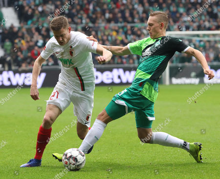 Augsburg's Alfred Finnbogason (L) in action against Bremen's Ludwig Augustinsson (R)  during the German Bundesliga soccer match between Werder Bremen and FC Augsburg  in Bremen, Germany, 10 February 2019.