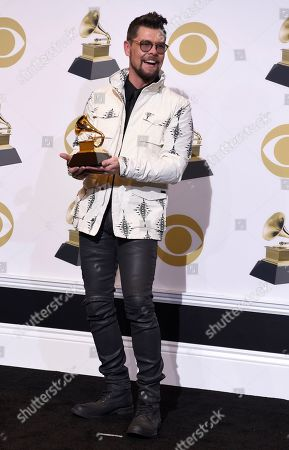 """Jason Crabb poses in the press room with the award for best roots gospel album for """"Unexpected"""" at the 61st annual Grammy Awards at the Staples Center, in Los Angeles"""