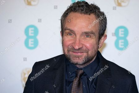 Eddie Marsan poses for photographers upon arrival at the BAFTA Film Awards in London