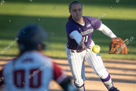 Cal State Fullerton Titan Classic. Northwestern infielder #11 Rachel Lewis throws a hit ball to first base for out during an NCAA softball game against Loyola Marymount on in Fullerton, Calif