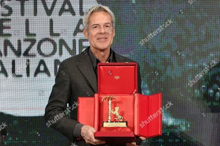 Claudio Baglioni poses with the 'Amico di Sanremo ' Award (Friends of Sanremo) during the final press conference