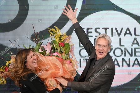 Stock Image of Claudio Baglioni gives to Director of Rai 1 Teresa De Santis a bouquet of flowers during the final press conference