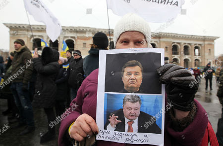 A supporter of Ukrainian presidential candidate Yulia Tymoshenko (not seen) seen holding a combo placard with photos of former Ukrainian President Viktor Yanukovich (up) and current Ukrainian President Petro Poroshenko (down) and saying No difference during the meeting with the electorate as part of her election campaign in Kiev.