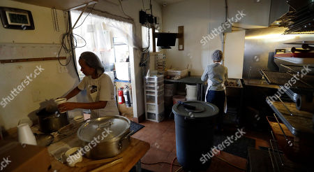 Sophia Otero, left, makes coffee, in Rockport, Texas, where the shop is using generators to keep the business open following the effects of Hurricane Harvey