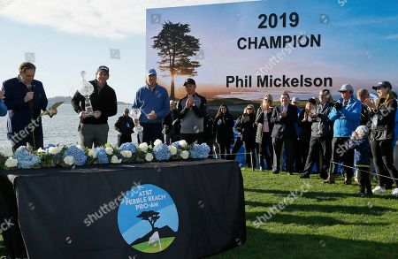 Stock Picture of Phil Mickelson, Jim Nantz, Paul Casey, Don Colleran. Phil Mickelson, second from left, holds his trophy on the 18th green of the Pebble Beach Golf Links after winning the AT&T Pebble Beach Pro-Am golf tournament, in Pebble Beach, Calif. At left is broadcaster Jim Nantz. Looking on are Paul Casey, of England, fourth from left, and his amateur partner, Don Colleran