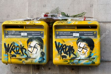 A rose is placed on vandalized mailboxes with swastikas covering the face of the late Holocaust survivor and renowned French politician, Simone Veil, before their renovation in Paris, Tuesday Feb.12, 2019. According to French authorities, the total of registered anti-Semitic acts rose to 541 in 2018 from 311 in 2017, a rise of 74 percent