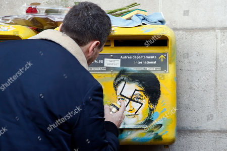 French street artist Christian Guemy, known as C215, cleans the vandalized mailboxes with swastikas covering the face of the late Holocaust survivor and renowned French politician, Simone Veil, in Paris, Tuesday Feb.12, 2019. According to French authorities, the total of registered anti-Semitic acts rose to 541 in 2018 from 311 in 2017, a rise of 74 percent