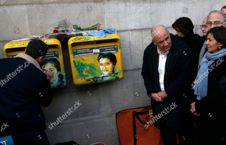 Paris mayor Anne Hidalgo, right, watches French street artist Christian Guemy, known as C215, cleaning the vandalized mailboxes with swastikas covering the face of the late Holocaust survivor and renowned French politician, Simone Veil, in Paris, Tuesday Feb.12, 2019. According to French authorities, the total of registered anti-Semitic acts rose to 541 in 2018 from 311 in 2017, a rise of 74 percent